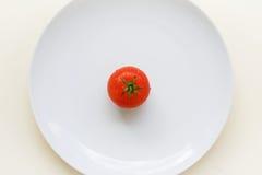 Reife Tomate auf einer weißen Platte Lizenzfreie Stockbilder