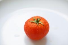 Reife Tomate auf einer weißen Platte Stockfoto