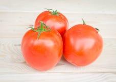 Reife Tomaten auf hölzernem Hintergrund Lizenzfreie Stockbilder