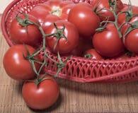 Reife Tomaten in einem roten Korb Bündel Tomaten von einem Korb Stockfotografie