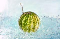 Reife Wassermelonen auf Abtropfbrett auf Tabelle auf hölzernem Hintergrund Lizenzfreies Stockfoto