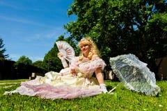 Reife Weinlesefrau im venetianischen Kostüm, das auf dem grünen Park mit weißem Regenschirm liegt Stockbild
