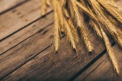 Reife Weizenährchen auf ländlichem Holztisch Stockbild