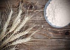 Reife Weizenähren und Weißmehl des Hintergrundes auf altem Weinleseholztisch Stockbild