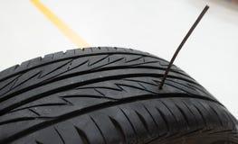 Reifen durchbohrt durch Eisenstock oder -nagel Autounfall oder Sicherheitsversicherungskonzept Stockbilder
