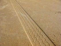 Reifen-Markierungen auf Strand-Sand Stockbild