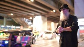 Reifen Sie den bärtigen touristischen Mann, der auf der Seite der Straße nachts wartet stock video