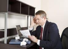 Reifen Sie den denkenden Mann beim Arbeiten an Einkommenssteuern Stockfoto