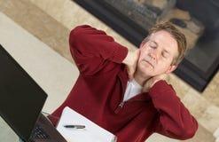 Reifen Sie den ermüdeten Mann beim zu Hause arbeiten Stockfotografie