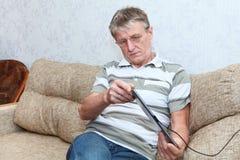 Reifen Sie den erwachsenen Mann, der an einem neuen Tablette-PC erforscht Stockfoto