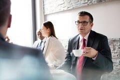 Reifen Sie den Geschäftsmann, der Kaffee bei der Unterhaltung mit männlichem Kollegen in der Bürocafeteria trinkt Stockfotos