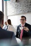 Reifen Sie den Geschäftsmann, der Kaffee beim Sitzen mit männlichem Kollegen in der Bürocafeteria trinkt Lizenzfreies Stockbild
