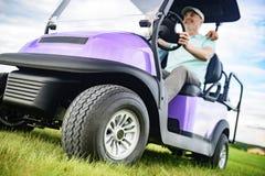 Reifen Sie den lächelnden Mann beim Fahren des Golfmobils Stockfotos