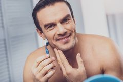 Reifen Sie den lächelnden Mann beim Rasieren seines Gesichtes stockfoto