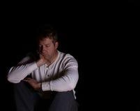 Reifen Sie den Mann, der Krise beim sich hinsetzen in der Dunkelheit zeigt Stockbild
