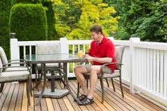 Reifen Sie den Mann, der Orangensaft beim Vorbereiten, im Freien zu lesen genießt Lizenzfreie Stockbilder