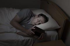Reifen Sie den Mann, der Zeit beim Versuchen überprüft zu schlafen Stockfotografie