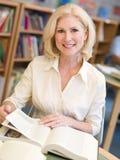 Reifen Sie den weiblichen Kursteilnehmer, der in der Bibliothek studiert stockbild