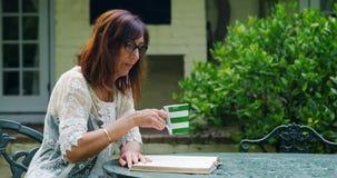 Reifen Sie die Frau, die Kaffee beim Ablesen eines Buches 4k trinkt stock footage