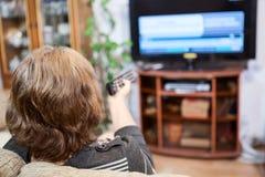 Reifen Sie die kaukasische Frau, die Fernsehkanäle mit Fernbedienung dreht Lizenzfreies Stockbild