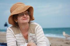 Reifen Sie Frau am Strand stockbilder