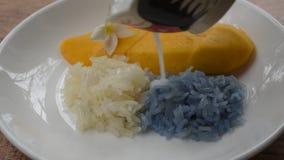 Reifen Sie Mango mit weißer und purpurroter Behandlungskokosmilch des klebrigen Reises auf Platte stock video footage