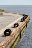 Reifen-Stoßdämpfer entlang konkretem Pier Stockfotos