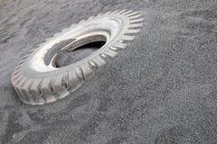 Reifenabdeckung unter dem schwarzen Sand stockfotos