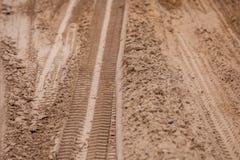 Reifenbahnen aus den Grund Weg von den Spurweiten der Straße 4X4 auf fahrendem Hintergrund des Landwüstenstrandstraßensandes Lizenzfreie Stockfotografie