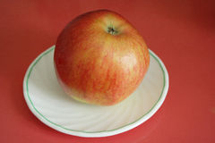 Reifer Apfel auf der weißen Platte Stockbild