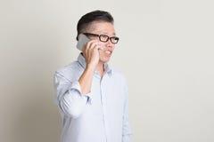Reifer asiatischer Mann, der Anruf auf Smartphone macht Lizenzfreies Stockfoto
