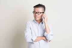 Reifer asiatischer Mann, der auf Smartphone spricht Stockfoto