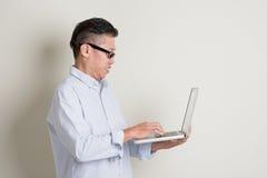 Reifer asiatischer Mann, der Computernotizbuch verwendet Stockbild