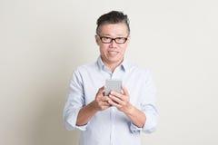 Reifer asiatischer Mann, der intelligentes Telefon verwendet Lizenzfreies Stockbild