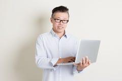 Reifer asiatischer Mann, der Laptop-Computer verwendet Stockfotos