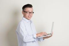 Reifer asiatischer Mann, der PC-Notizbuch verwendet Stockfoto