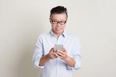 Reifer asiatischer Mann, der Smartphone verwendet Lizenzfreies Stockfoto