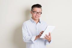 Reifer asiatischer Mann, der Tabletten-PC verwendet Lizenzfreie Stockfotografie