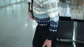 Reifer attraktiver Mann in der weißen Strickjacke und in den Gläsern sitzt im Flughafenaufenthaltsraum Sie kündigten seinen Flug, stock video footage