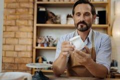 Reifer bärtiger Ceramist, der seine Handarbeit betrachtet stockfoto