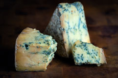 Reifer blauer moderiger Käse des Stiltons - dunkler Hintergrund Stockfotografie