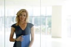 Reifer blonder lächelnder Geschäftsfraustand hinter Glastür Lizenzfreie Stockfotografie