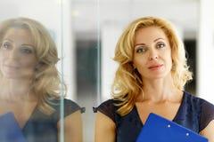 Reifer blonder lächelnder Geschäftsfraustand nahe Glastür Lizenzfreie Stockbilder