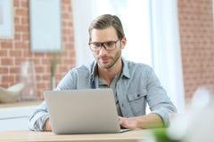Reifer blonder Mann, der an Laptop arbeitet Lizenzfreie Stockfotografie
