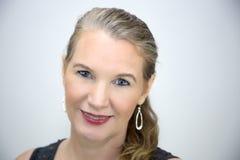 Reifer blonder weiblicher Hauptschuß, der das Kamera-Lächeln betrachtet Lizenzfreies Stockfoto