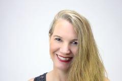 Reifer blonder weiblicher Hauptschuß, der Kamera betrachtend lächelt Stockfotos