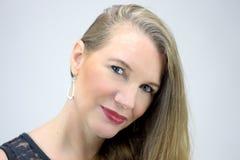Reifer blonder weiblicher Hauptschuß, der Kamera betrachtend lächelt Stockfoto
