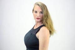 Reifer blonder weiblicher Torso schoss das Betrachten der Kamera von der Seite Stockfotos