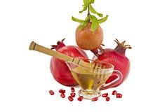 Reifer bunter Granatapfel und Honig auf weißem Hintergrund Stockfotografie