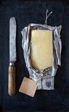 Reifer Cheddar-Käse eingewickelt im rustikalen Papier und in einem Weinlesemesser Lizenzfreie Stockfotos
